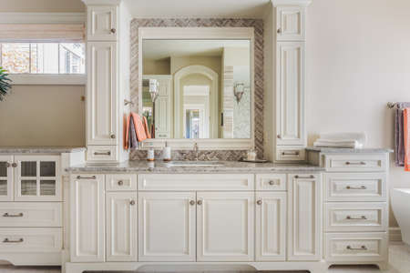 bathroom mirror: Elegant Cabinetry and fine craftsmanship lend an upscale touch to a full master bathroom Stock Photo