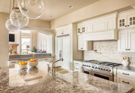 Kitchen with Island, Sink, Cabinets, and Hardwood Floors and View of Living Room
