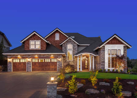exterior wall: Front exterior of luxury home in evening Stock Photo