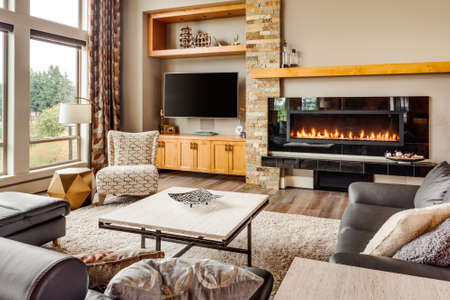 living room sofa: Beautiful living room with hardwood floors and roaring fire in fireplace Stock Photo