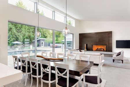 nowy: Piękny salon i jadalnia z kominkiem i widokiem na patio z basenem i dużych przesuwnych szklanych drzwi Zdjęcie Seryjne