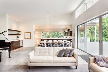 Beautiful living room in new luxury home with view of dining room table and kitchen