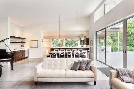 piano: Hermosa sala de estar en casa de lujo con vista a la mesa del comedor y cocina