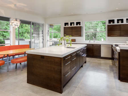 Kitchen with Island, Sink, Cabinets and Dining Table in New Luxury Home Foto de archivo