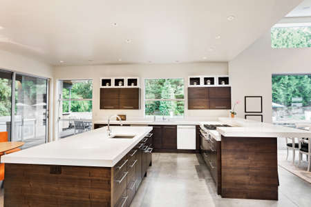 island: Kitchen with Island, Sink, Cabinets and view of trees