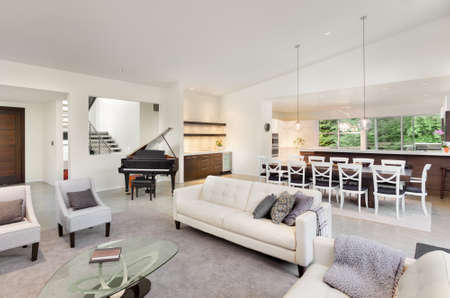 Living room interior in new luxury home with entryway, piano, couch, view of dinging room table, wet bar, and kitchen