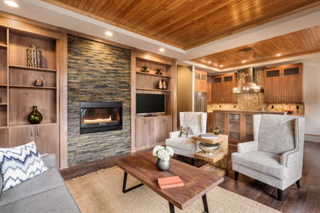 fireplace family: Living room interior with wood strip ceiling and view of kitchen in luxury home Stock Photo