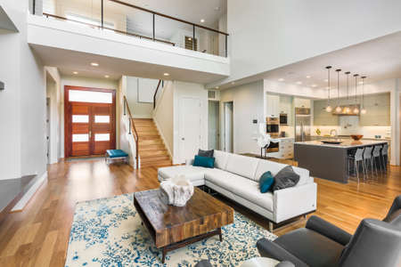contemporary interior: living room in luxury home with view of kitchen, entryfoyer, front door, stairs, and loft area