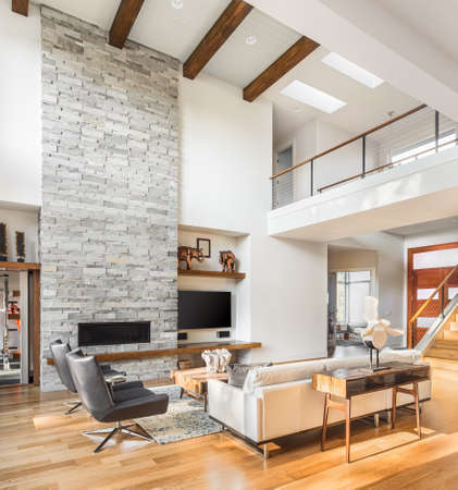 contemporary living room: living room interior with hardwood floors and fireplace in new luxury home with vaulted ceiling, loft area, and entrywayfoyer