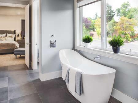 Bañera en baño principal en la nueva casa de lujo con vista del dormitorio principal y barrio con árboles a través de la ventana Foto de archivo - 47256462