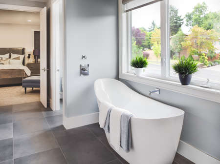 cuarto de baño: Bañera en baño principal en la nueva casa de lujo con vista del dormitorio principal y barrio con árboles a través de la ventana Foto de archivo