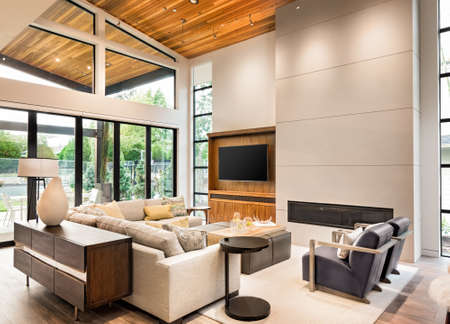 living room interior with hardwood floors, vaulted ceiling, and fireplace in new luxury home