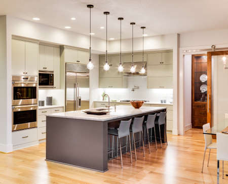 contemporary interior: Kitchen with Island, Sink, Cabinets, and Hardwood Floors in New Luxury Home