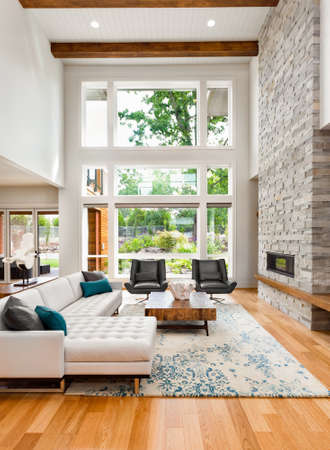 family in living room: living room interior with hardwood floors, huge bank of windows, tall vaulted ceiling, and fireplace in new luxury home Stock Photo