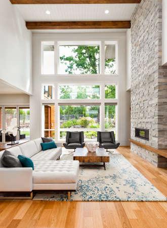 Wohnzimmer-Interieur mit Holzböden, riesige Bank von Fenstern, hohen Gewölbedecke und Kamin in neuen Luxus-Haus Standard-Bild