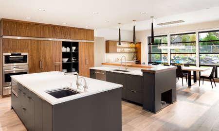 canicas: Interior de la cocina con dos islas, dos lavabos, gabinetes y pisos de madera en Nueva Casa de lujo