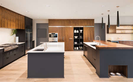 kitchen: Kitchen Interior with Two Islands,  Two Sinks, Cabinets, and Hardwood Floors in New Luxury Home