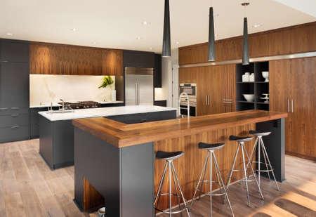Interno di cucina con due isole, due lavandini, armadi, e pavimenti in legno di nuova casa di lusso Archivio Fotografico - 47256597