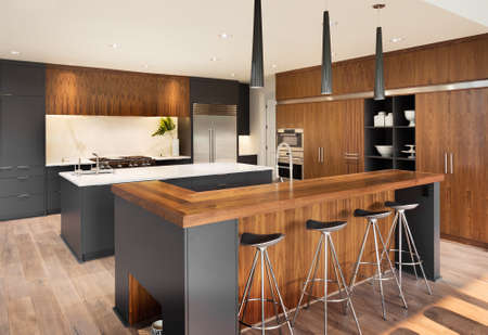 condo: Kitchen Interior with Two Islands,  Two Sinks, Cabinets, and Hardwood Floors in New Luxury Home