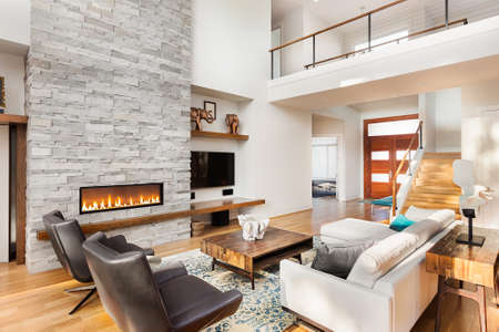family in living room: Beautiful living room with hardwood floors and fireplace in new luxury home