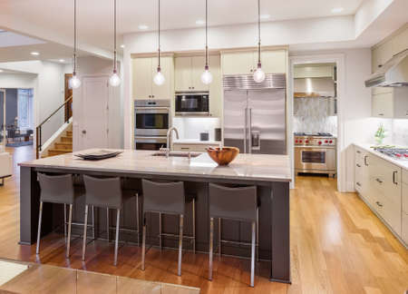 hardwood: Kitchen Interior with Island, Sink, Cabinets, and Hardwood Floors in New Luxury Home Stock Photo