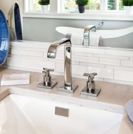 bathroom interior detail in new luxury home: sink with faucet and reflection of bathtub