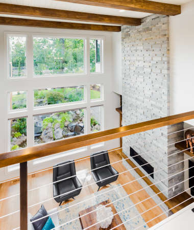 living room window: living room interior with hardwood floors and view of lush vegetation Stock Photo