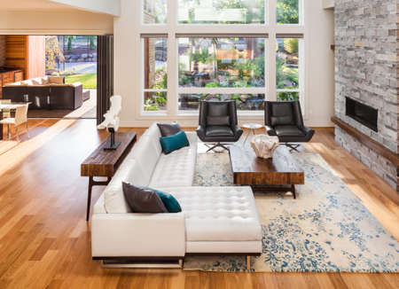 living room interior with hardwood floors and fireplace in new luxury home. View of outdoor patio