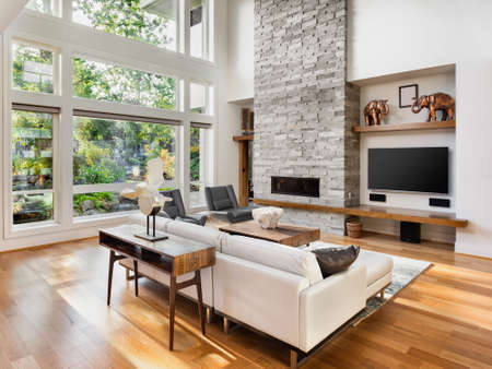 living room interior with hardwood floors, fireplace, and large bank of windows with view of lush vegetation, in new luxury home