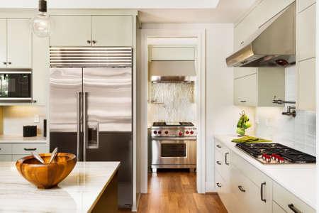 estufa: Interior de la cocina con isla, fregadero, armarios, y pisos de madera en Nueva Casa de lujo