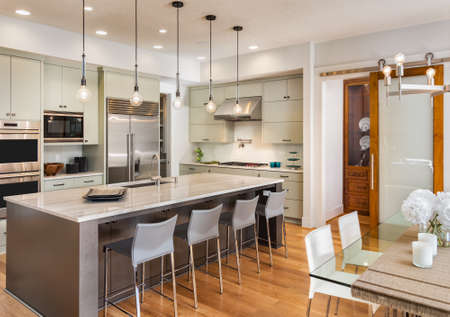 kitchen interior and dining room in new luxury home, with island, pendant lights, stainless steel appliances, and hardwood floors Banque d'images