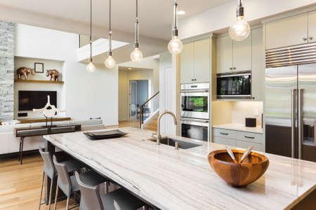 Interior de la cocina con isla, fregadero, armarios, y pisos de madera Foto de archivo