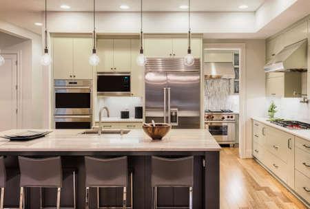Keuken Interieur met Island, gootsteen, kasten en hardhouten vloeren in New Luxury Home Stockfoto