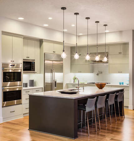 nobody real: Kitchen Interior with Island, Sink, Cabinets, and Hardwood Floors in New Luxury Home Stock Photo