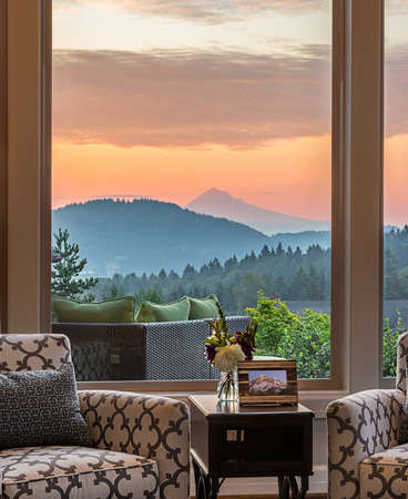 furniture home: living room interior detail in luxury home with colorful sunset sky backdrop