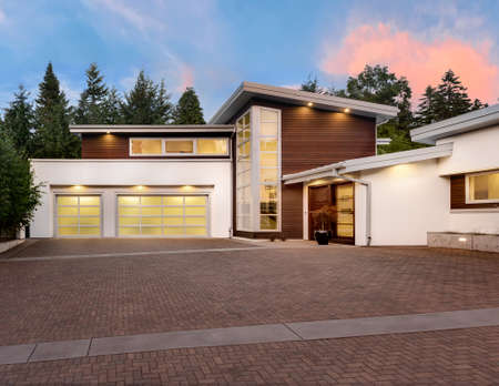 Facade of large, luxury home with expansive driveway with colorful sunset backdrop