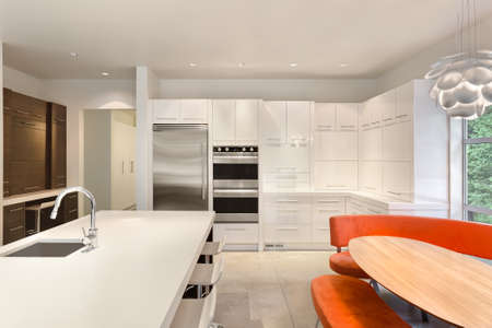 Kitchen with Island, Sink, Cabinets, and Hardwood Floors in new house Stock Photo