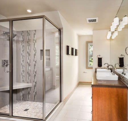 Large furnished bathroom in luxury home with tile floor, two sinks, fancy cabinets, large mirror, and shower