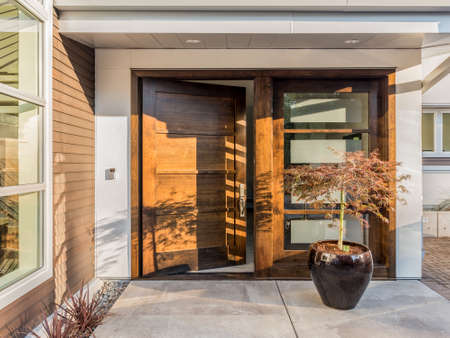 Beautiful Wood Door as Entrance to New Luxury Home: Large and Wide Hardwood Door with Windows and Potted Plant to Right of Door in Exterior of Beautiful House. Cement Patio. Door is Slightly AjarOpen