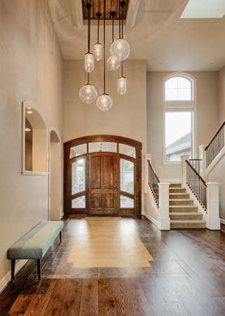 집안의 아름 다운 로비; 신축 럭셔리 하우스에서 계단, 펜던트 조명, 하드 우드 플로어, 타일, 벤치 및 아치형 천장이있는 출입구