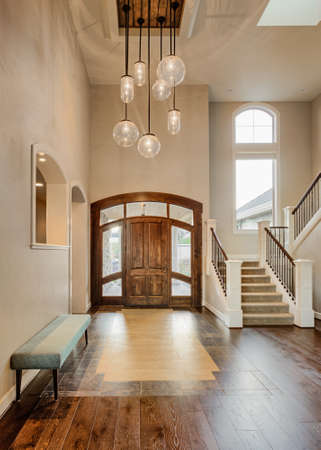 hardwood: Beautiful Foyer in Home; Entryway with Stairs, Pendant Lights, Hardwood Floor, Tile, Bench, and Vaulted Ceilings in New Luxury House