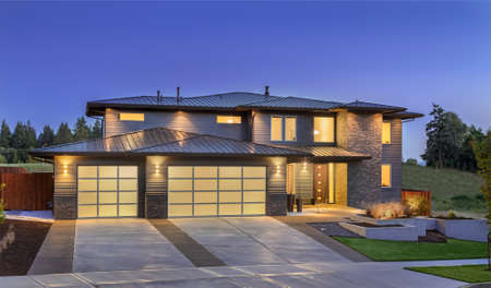 garage on house: Front elevation of luxury home in evening
