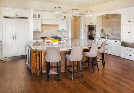 mooie, grote keuken interieur in nieuwe luxe huis met kookeiland, koelkast, fornuis, afzuigkap, en hardhouten vloeren Stockfoto