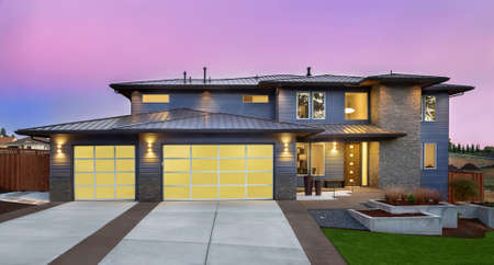 Beautiful Exterior of New Luxury Home at Sunset with Colorful Sky Фото со стока
