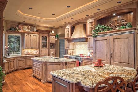 hermoso, amplio interior de la cocina en la casa de lujo con isla, refrigerador, estufa, campana, y pisos de madera Foto de archivo