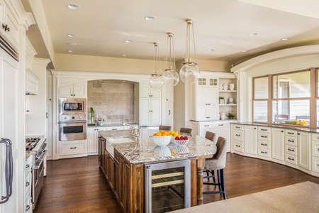 hermoso, amplio interior de la cocina en la casa de lujo con isla, refrigerador, estufa, campana, y pisos de madera