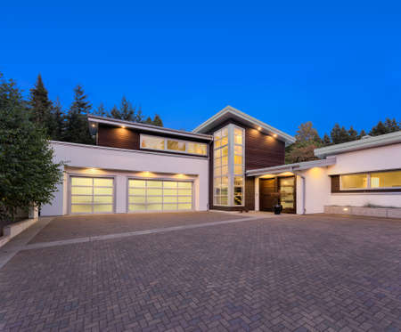 garage on house: Facade of large, luxury home with expansive driveway with colorful sunset backdrop
