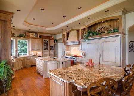 mostradores: hermoso, amplio interior de la cocina en la casa de lujo con isla, refrigerador, estufa, campana, y pisos de madera
