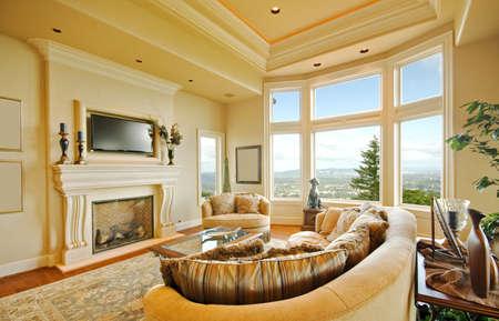 Prachtige woonkamer interieur in luxe huis met open haard, TV, en weids uitzicht met Blue Sky Stockfoto