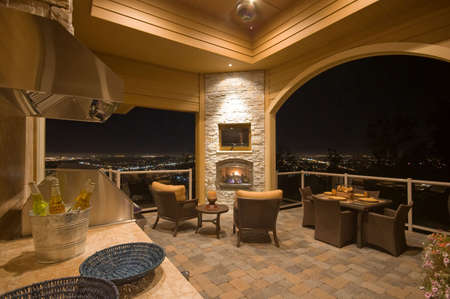 stone fireplace: Beautiful Patio with View at Night on Exterior of Luxury Home